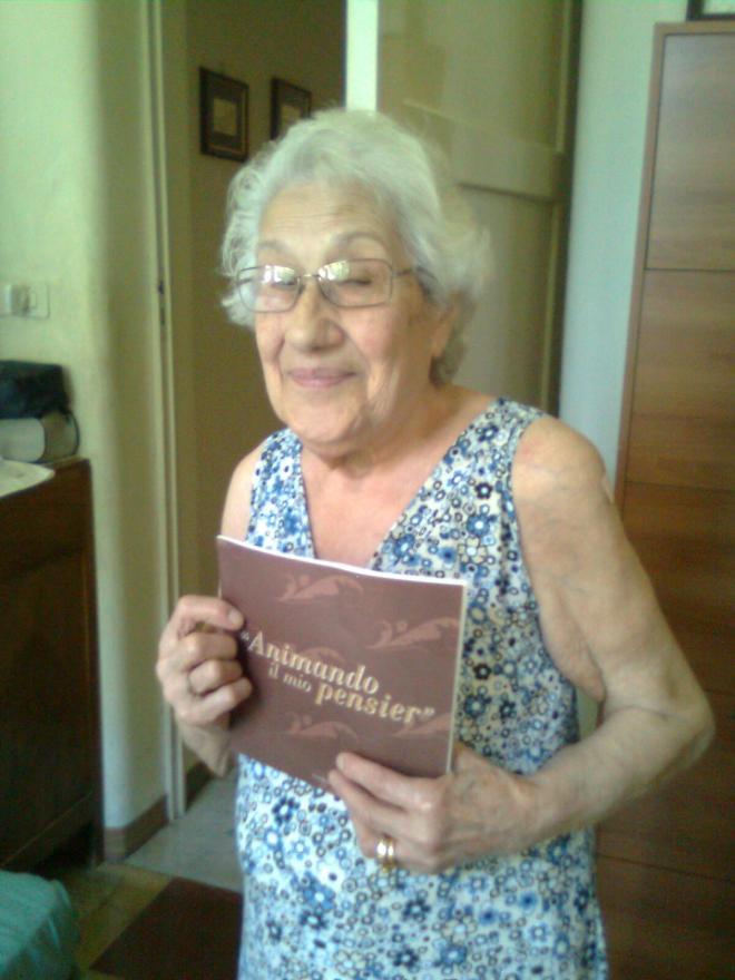 """La maestra  Michelina Andreacchio Rodofili  con gioia tiene in mano il libro  """"Animando il mio pensier"""""""